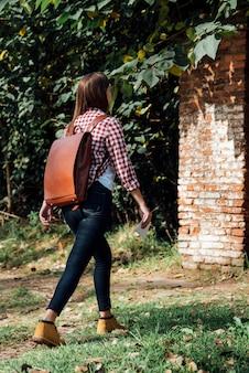Девушка с рюкзаком гуляя в природу