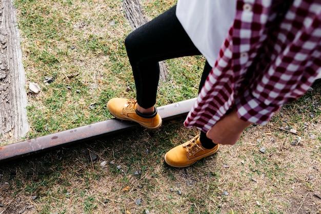 Высокий угол девушка с ногой на железной дороге