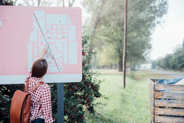 Вид сзади девушка с рюкзаком, проверка карты в парке