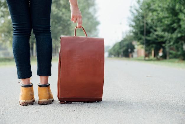 道路上のビンテージバックパックを持つ旅行者