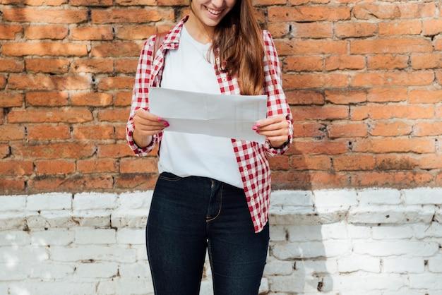 Улыбающаяся девушка проверяет карту кирпичной стеной
