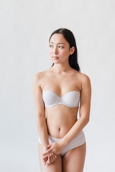 Молодая азиатская брюнетка в бюстгальтере и трусах на белом фоне