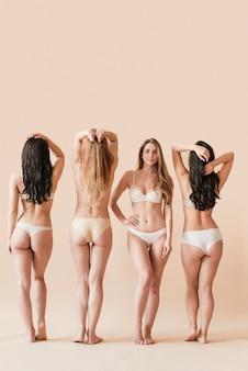 下着姿で立っている多様な女性のグループ