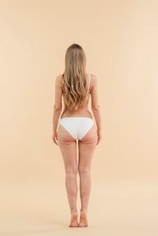 白いランジェリーを着ている長い髪の金髪女性