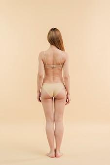 下着姿でポーズをとって髪の長いスリムな赤毛の女性