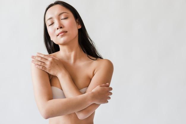 Мечтательная азиатка в лифчике обнимает себя