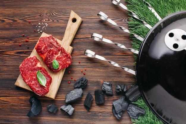 Прибор для барбекю с сырым стейком на разделочной доске над деревянным столом