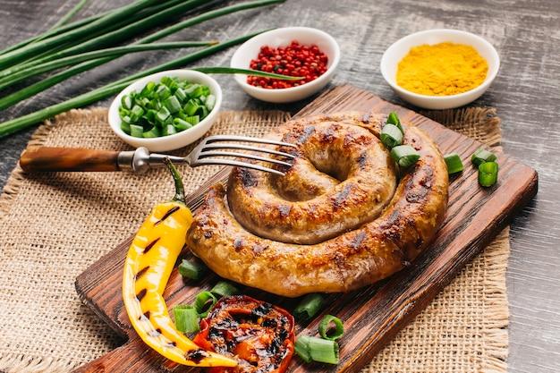 Крупный план жареной колбасы улитки на разделочной доске