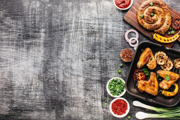 Вид сверху жареного мяса и овощей на деревянном текстурированном фоне