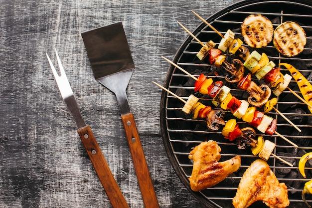木製の背景上のバーベキューグリルで焼き肉の準備