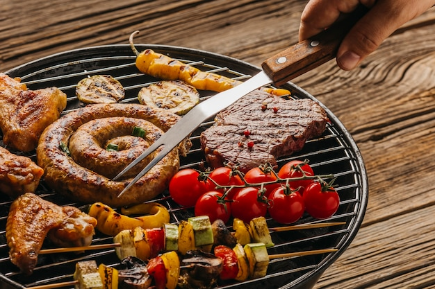 Человеческая рука готовит жареное мясо и колбаски на гриле