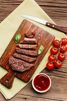 木製のまな板の上の赤いトマトソース炒めステーキのスライス