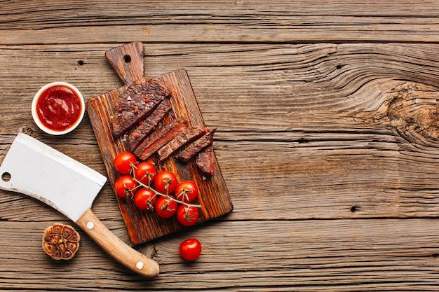Кусочек стейка-гриль и красного помидора черри на разделочной доске над деревянным столом