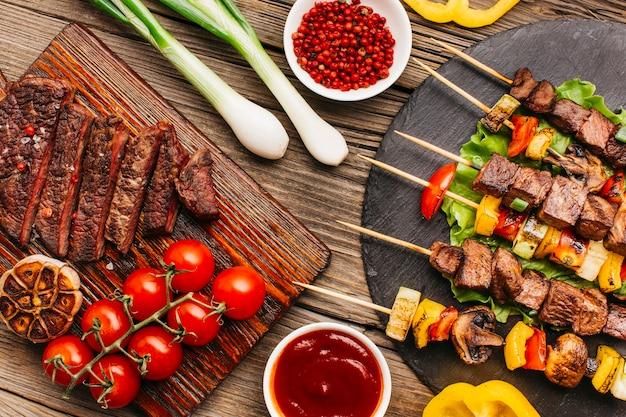 Вкусное мясо на гриле и стейк из свежих овощей