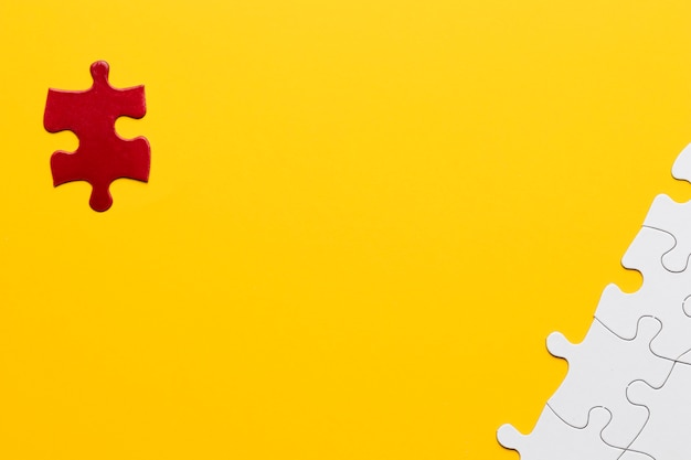 Красный пазл стоит отдельно от белого пазла на желтом фоне
