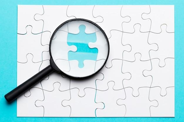 青い背景上の行方不明のパズルに虫眼鏡の高角度のビュー