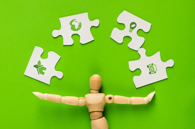緑の上の人間の指で白いパズルのピースのエコロジーアイコン