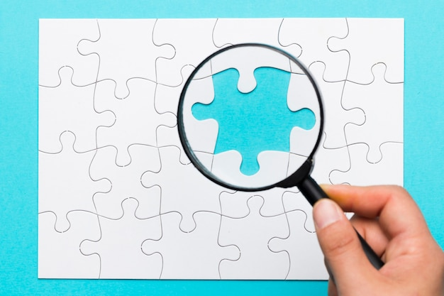 行方不明のパズルのピースの上に虫眼鏡を持っている人間の手
