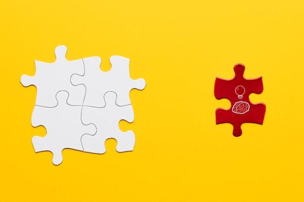 黄色の背景上の白い共同パズルのピースの近くに立っている赤いパズルのピース上のアイデアアイコン