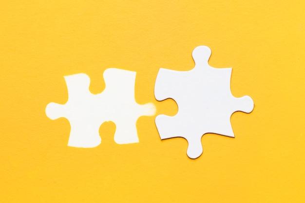 黄色の表面に段ボールのパズルのピースとパズルのピースの白スタンプ