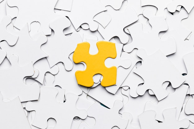 Высокий угол зрения желтого головоломки над белыми кусочками головоломки