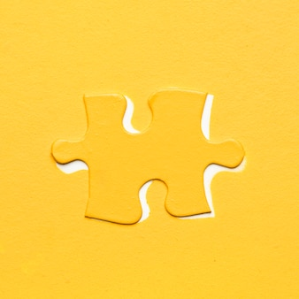 色付きの背景上の黄色のパズルのピース