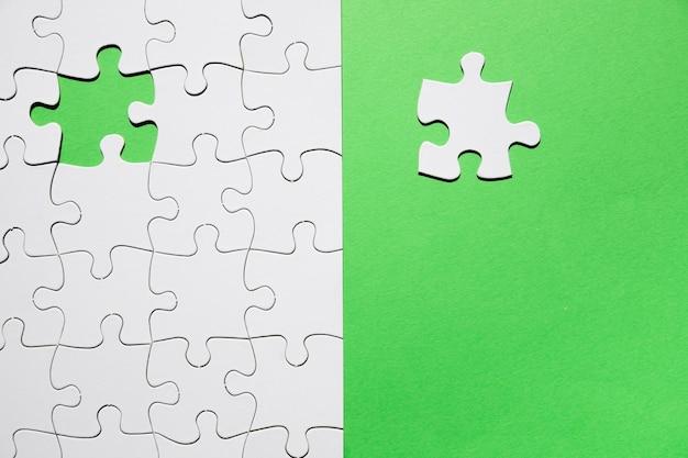 ミッションを完了するために緑色の背景で行方不明のパズルの最後の部分