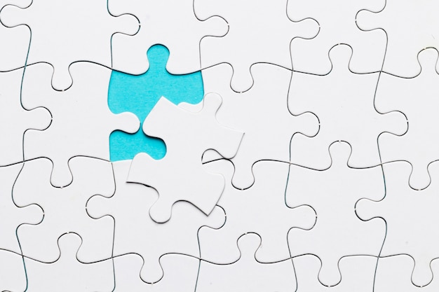 行方不明のパズルのピースを持つ白いジグソーパズルグリッド