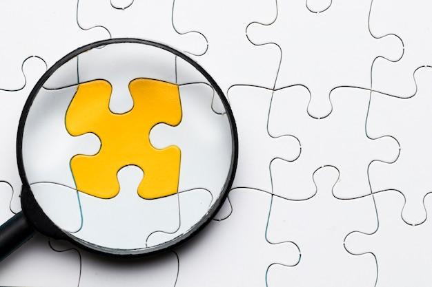 白いパズルと接続されている黄色のパズルのピースの上の虫眼鏡のクローズアップ