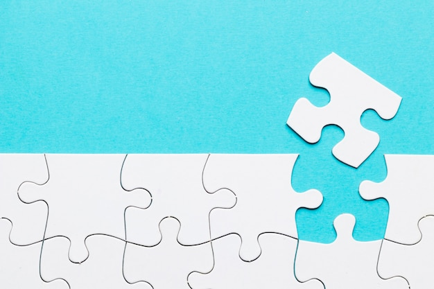 青の背景に白のパズルグリッドで行方不明のパズルのピース