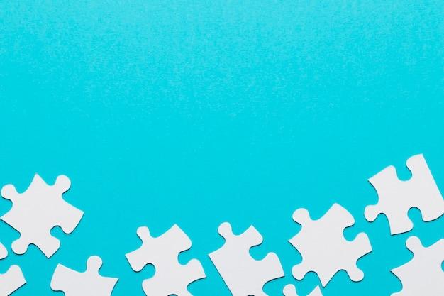 青い背景の下部にある別々のジグソーパズルのピース