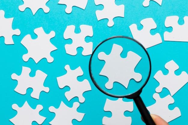 青い白い背景の上の虫眼鏡を通して見た白いジグソーパズルのピース