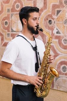 Боком человек среднего выстрела играет на саксофоне с геометрическим фоном