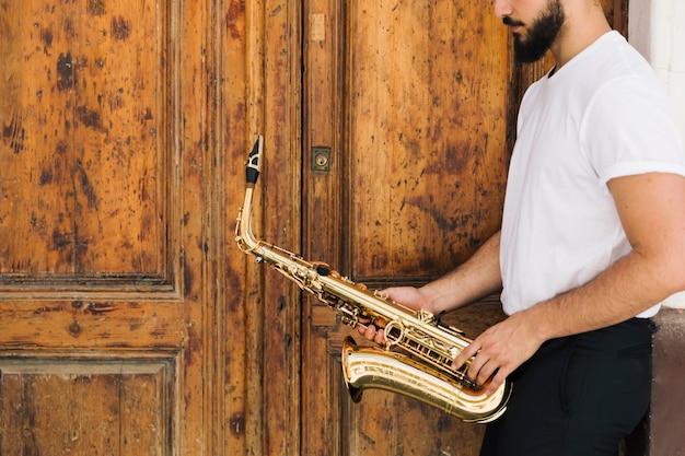 木製の背景を持つ横向きサックス奏者