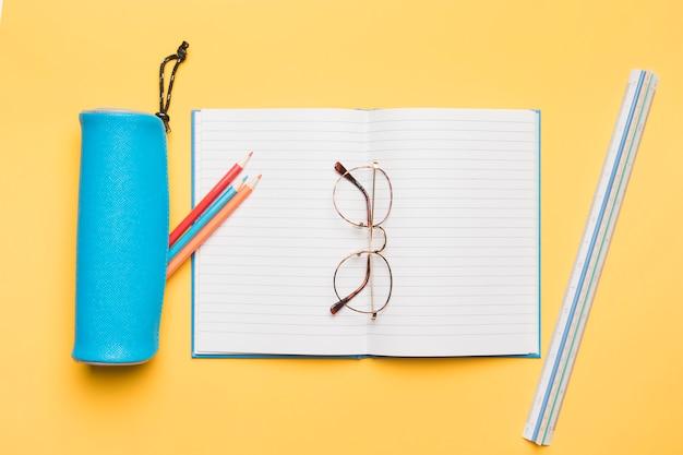 空白のページで開かれたノートブックの上に横たわるメガネ