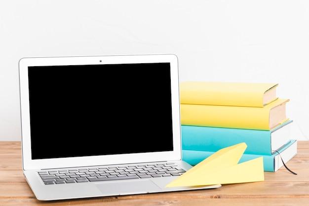 本やテーブルの上のノートパソコンの山