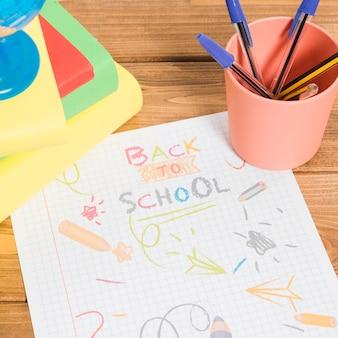 本と鉛筆で木製のテーブルに学校に戻って紙に色で描く