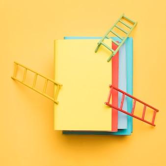 黄色の背景にカラフルな空白の本のスタック上の明るいはしご