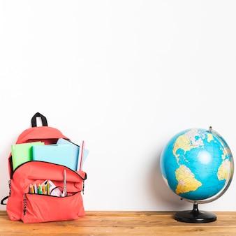 テーブルの上の地球とスクールバッグ
