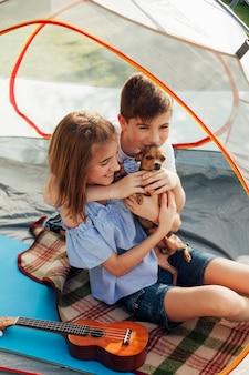テントに座って彼らのペットを愛する兄と妹