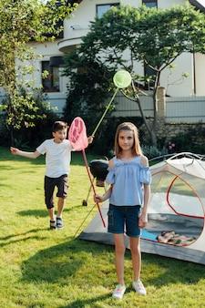Брат и сестра ловят бабочек и жуков сеткой для бабочек в парке