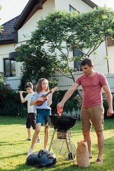 彼の娘がウクレレを演奏しながらバーベキューグリルで食べ物を準備する男