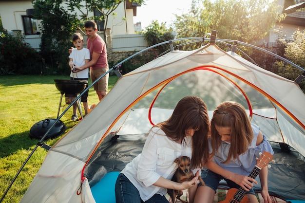 母と娘のテントで彼らのペットと遊ぶ