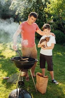 バーベキューグリルで料理をする彼の息子を持つ男