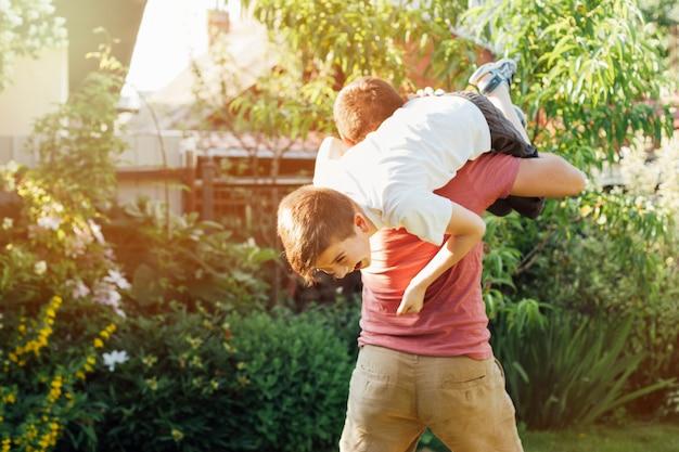 遊び心のある父は公園で肩に彼の微笑の息子を運ぶ