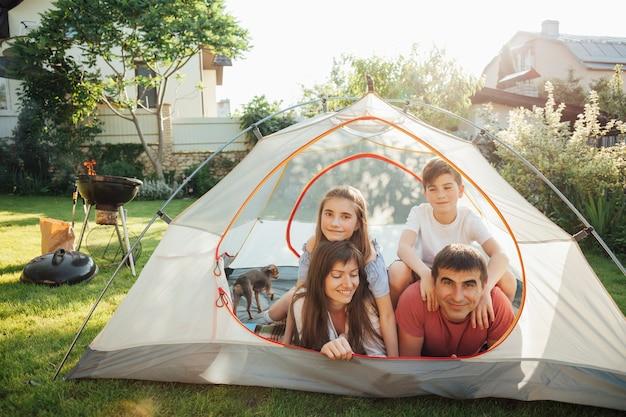 Родители с детьми лежат на палатке во время пикника