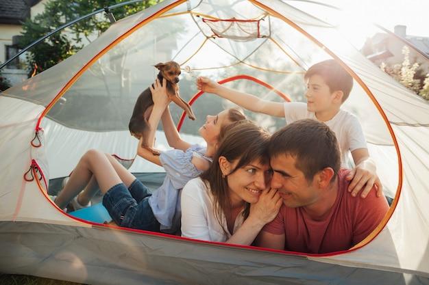 ロマンチックなカップルは彼らの子供たちがテントの中で犬と遊んでいる間お互いを見て