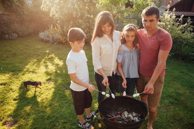 家族のバーベキューの近くに立って、公園でマシュマロを焙煎