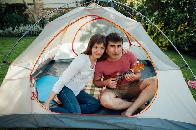 カメラを見てテントの中で彼の妻と座っているウクレレを弾く男