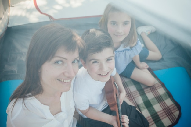 女性とテントの中で座っている彼女の子供たちの高角度のビュー